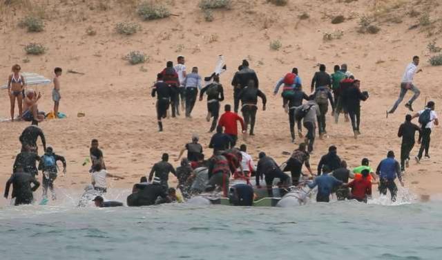Imigrantes chegam a praia na Espanha, observados por turistas