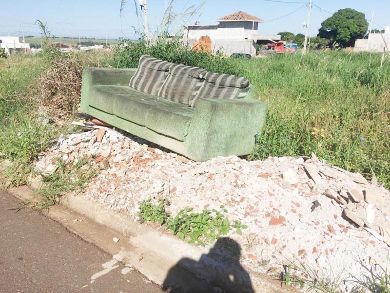 Problema crônico, lixo jogado em terrenos conta até com sofá